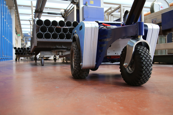 Zallys M4 electric tugger moves trolley with steel tubes in a manufacturing company