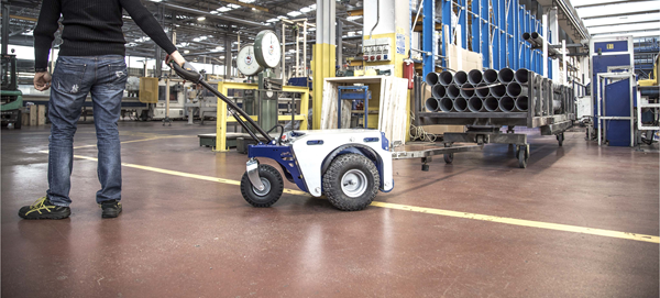 Zallys M4 electric tugger pulls trolley with pipes in manufacturing companies